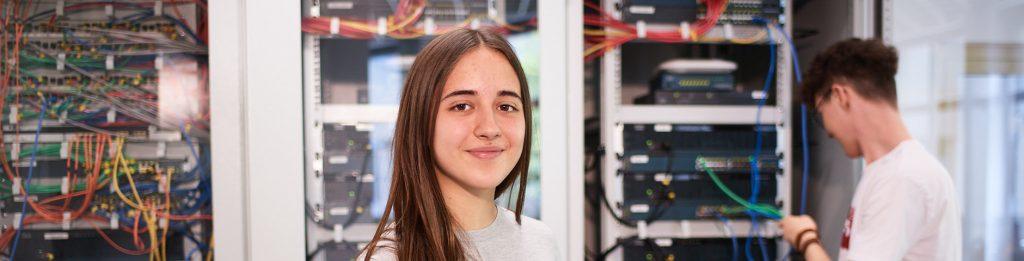Schülerin vor einem Netzwerkschrank in der IT-Academy