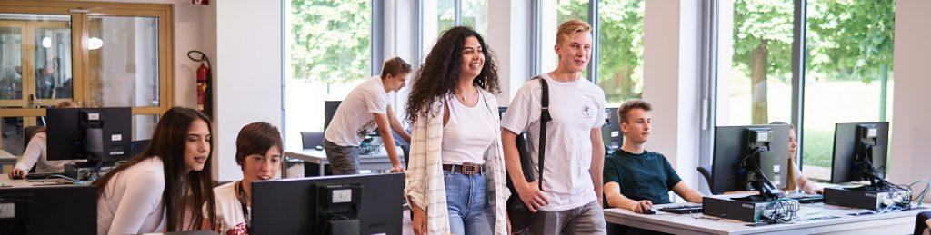 Eine Schülerin und ein Schüler in der IT-Academy gehen nach vorne